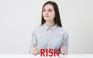 "Red ""Risk"" with woman with fork and knife at table"