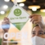 Woman in Mask at Storefront Placing 'Open' Sign